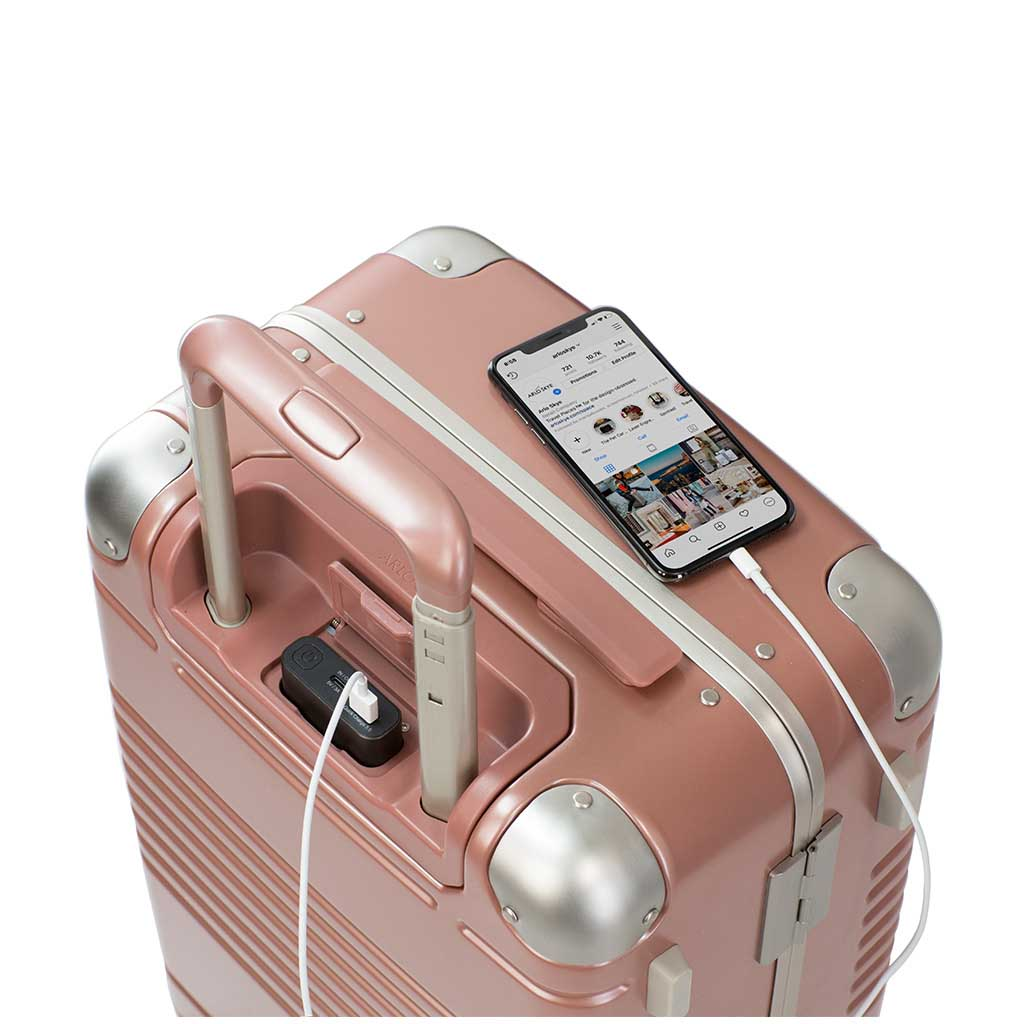 Top down view of frame carry-on max in rose gold showing the spare charger in use