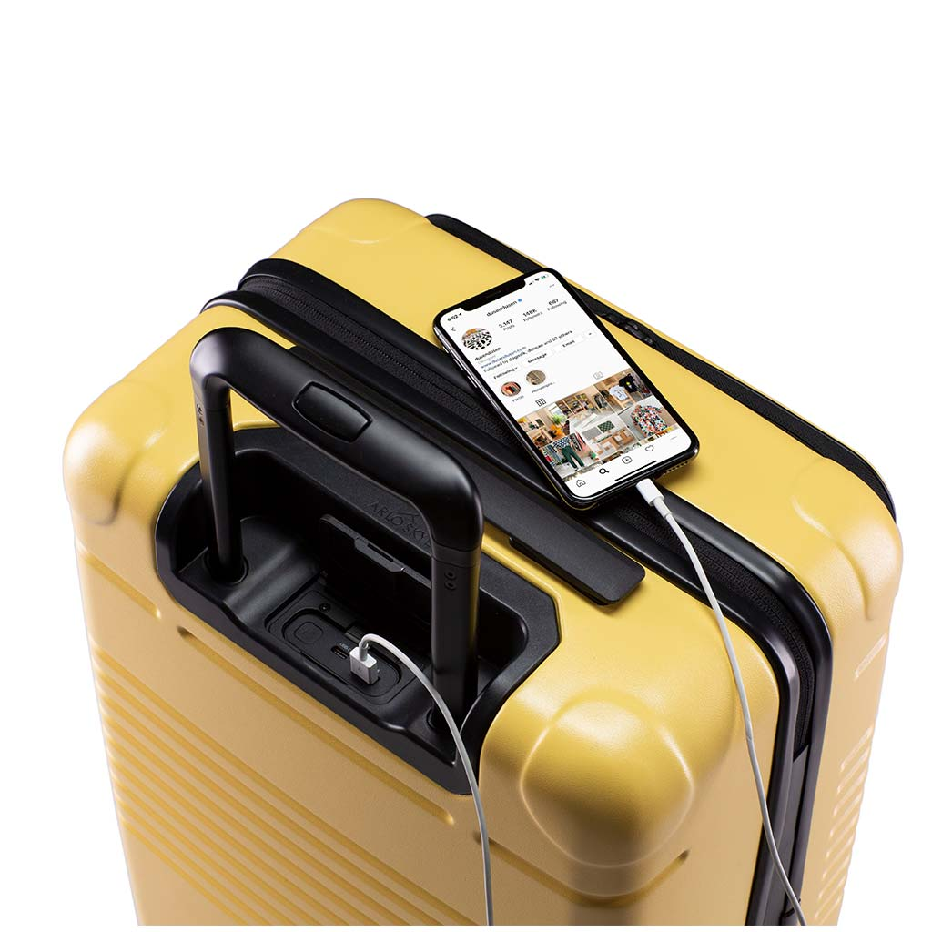 Top down view of the zipper carry-on max with front pocket in yellow with spare charger in use