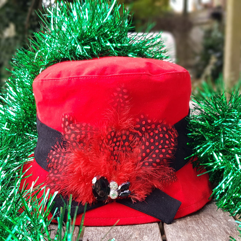 Red velour rain hat with black band with feathers and a jewl