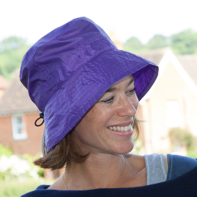 Purple packable summer rain hat on woman