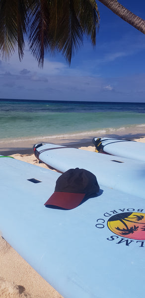 Green wax sports cap lying on surf board on a beach