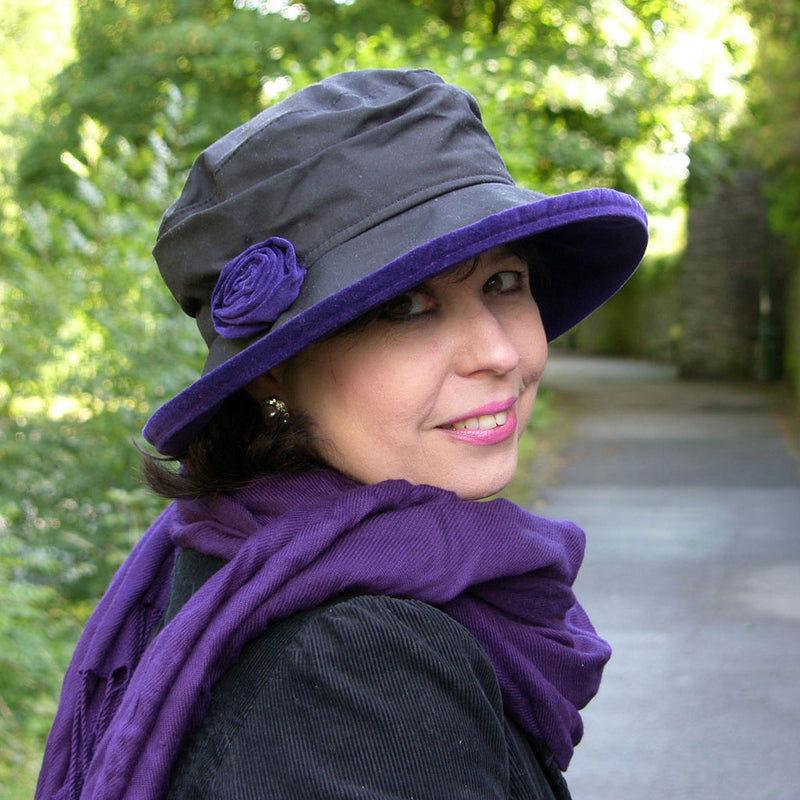 Lady wearing a black waxed ladies hat with purple trim and flower to one side