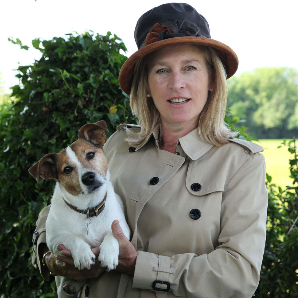 Peak And Brim Zara Brown Wax Rain Hat With Tan Suede Trim on Woman Holding Dog