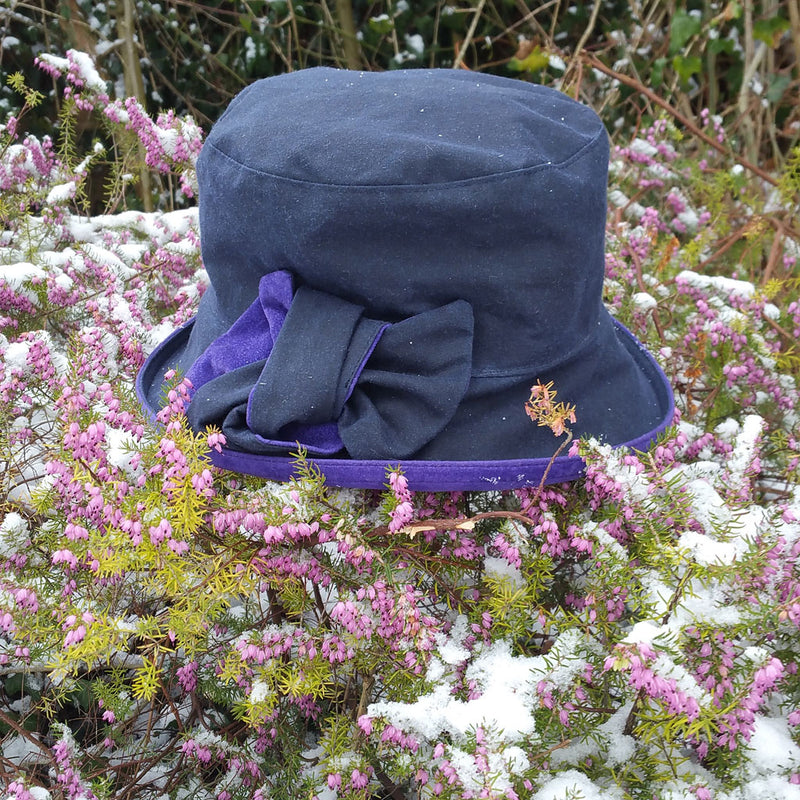 peak and brim zara navy waxed cotton rain hat with violet suedette trim and bow