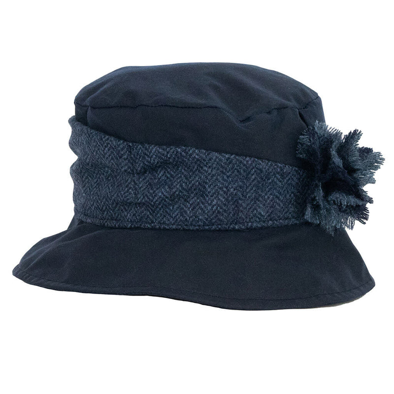 ladies navy waxed rain hat with tweed trim round crown of hat with tweed flower