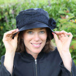 ladies navy waxed rain hat with tweed trim and bow on woman holding onto her hat