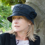 ladies navy waxed rain hat with tweed trim round crown of hat with tweed flower on woman