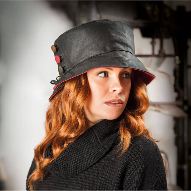 woman wearing black waxed bucket style hat with red underbrim and decorative buttons to one side of hat