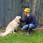 woman wearing yellow rain hat with navy underbrim with dog