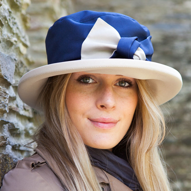 woman wearing navy rain hat with cream bow and under brim