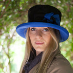 ladies black rain hat with royal blue bow and under brim on woman
