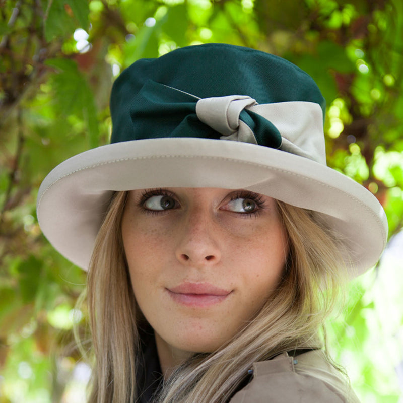 ladies green rain hat with cream bow and under brim on woman