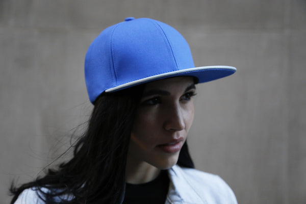 girl wearing a six panel Papa Originals baseball cap with light blue cotton canvas crown and sky blue Italian lambskin leather brim