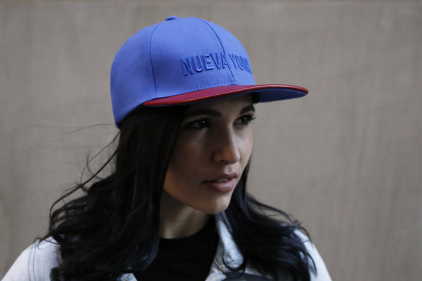 girl wearing a six panel Papa Originals baseball cap with blue cotton canvas crown and red Italian lambskin leather brim and Nueva York embroidery
