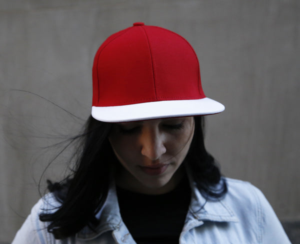 girl wearing a six panel Papa Originals baseball cap with red cotton canvas crown and white Italian lambskin leather brim