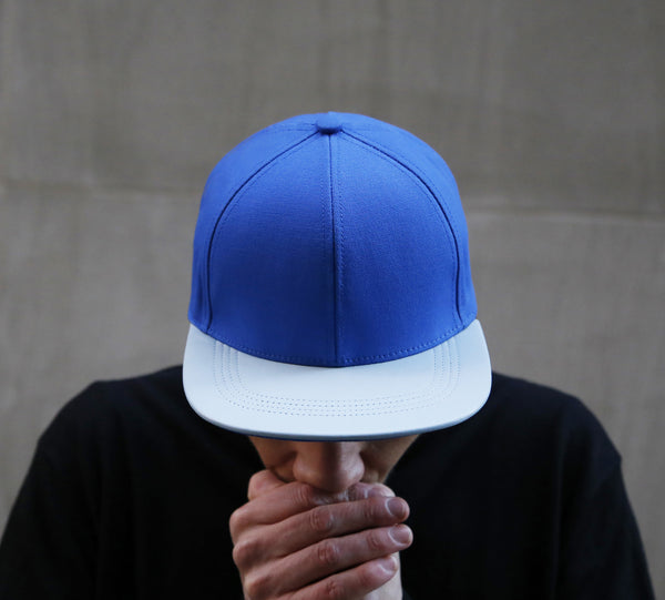 guy wearing a six panel Papa Originals baseball cap with light blue cotton canvas crown and sky blue Italian lambskin leather brim hat casquette
