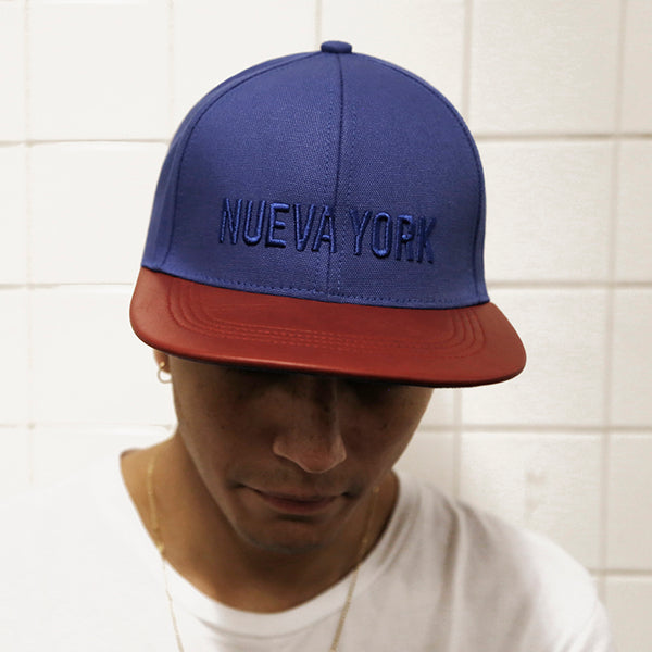 guy wearing a six panel Papa Originals baseball cap with blue cotton canvas crown and red Italian lambskin leather brim and Nueva York embroidery  gorra casquette hat