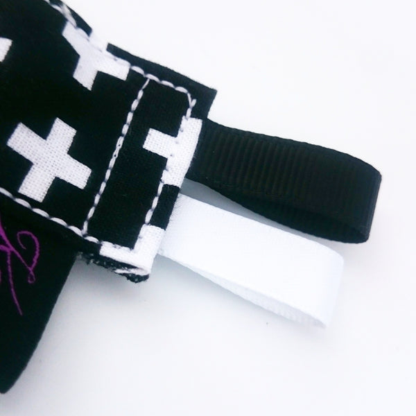 monochrome cross wooden ring teethers with ribbon tags