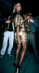 Model Lauren Hutton in a mini vintage gold dress