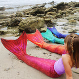 Girls in mermaid tails on the beach