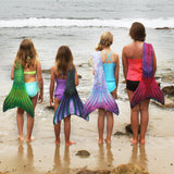 mermaid girls in mermaid tails swimming on the beach