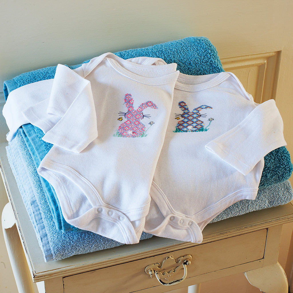 Cross-stitch bunny baby-grows in blue and pink