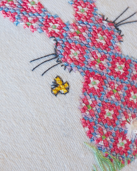 Pink cross stitch bunny baby-grow close up