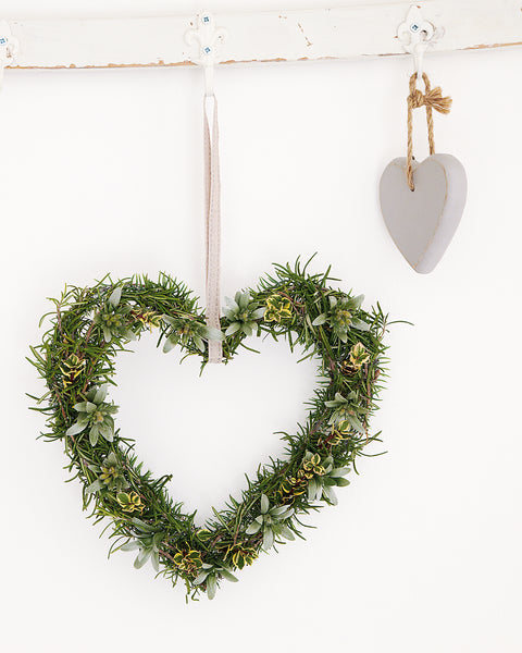 Rosemary heart shaped wreath hanging on a white wall