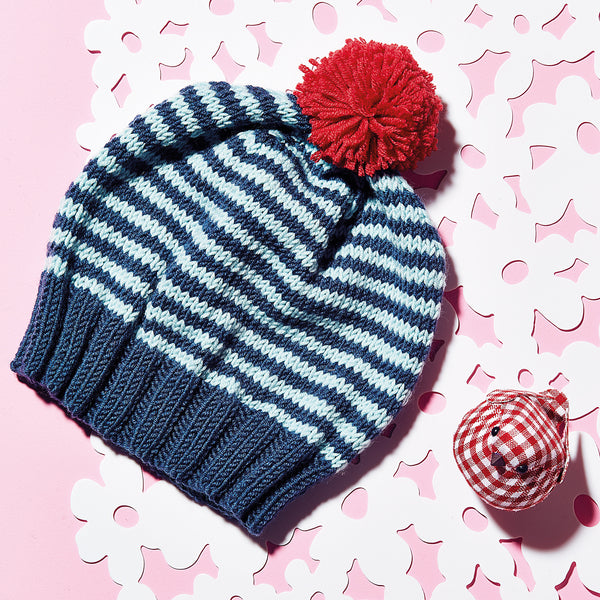 knitted blue striped hat with a red pom pom