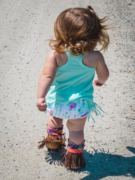 Brand Rep Girl wearing out Cactus Bummies, with a turquoise fringed shirt, and fringed booties.