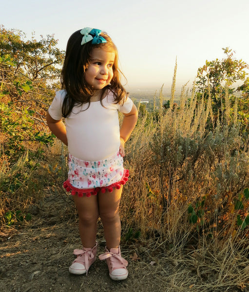 Brand Rep Girl wearing our cactus bummies with hot pink pom-poms, and a white shirt and converse sneakers.