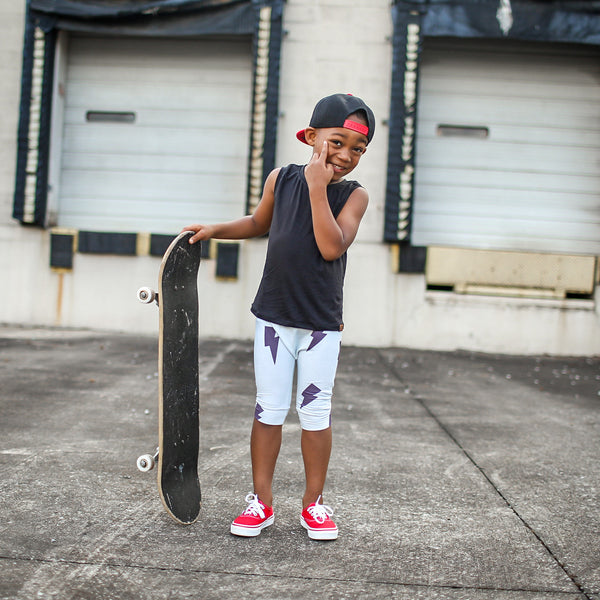 young model wearing baseball hat smiling with black bamboo tank top on and red shoes