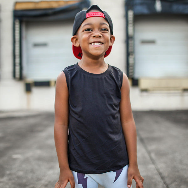 young model wearing baseball hat smiling with black bamboo tank top on