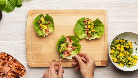Placing salmon and avocado mixture into lettuce wraps