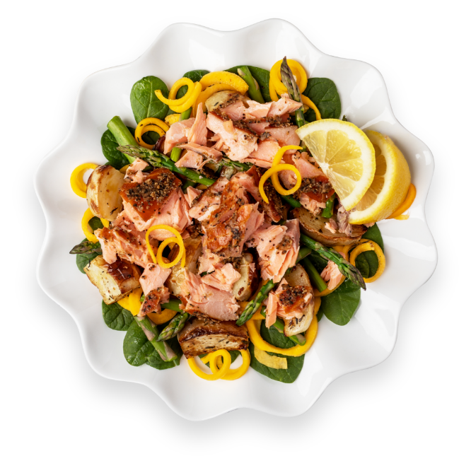 Salmon pasta spinach dish in a white serving plate with lemons