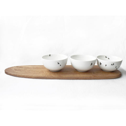 Three white snack bowls with bird print and wooden tray