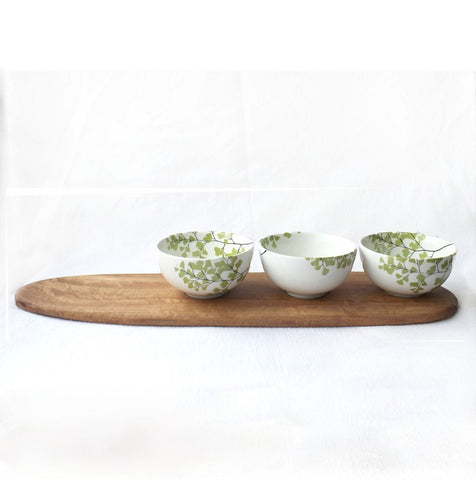 Three white tapas bowls with fern print and wooden tray
