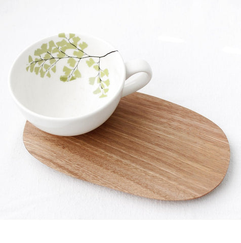 White cappuccino cup with fern design and wooden saucer