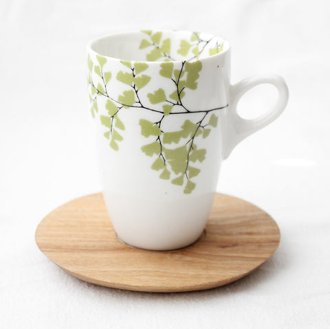White coffee mug with fern print and wooden saucer