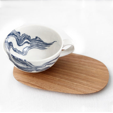 White tea cup with indigo mineral print and wooden Saucer