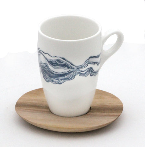 White coffee mug with blue mineral print and wooden saucer
