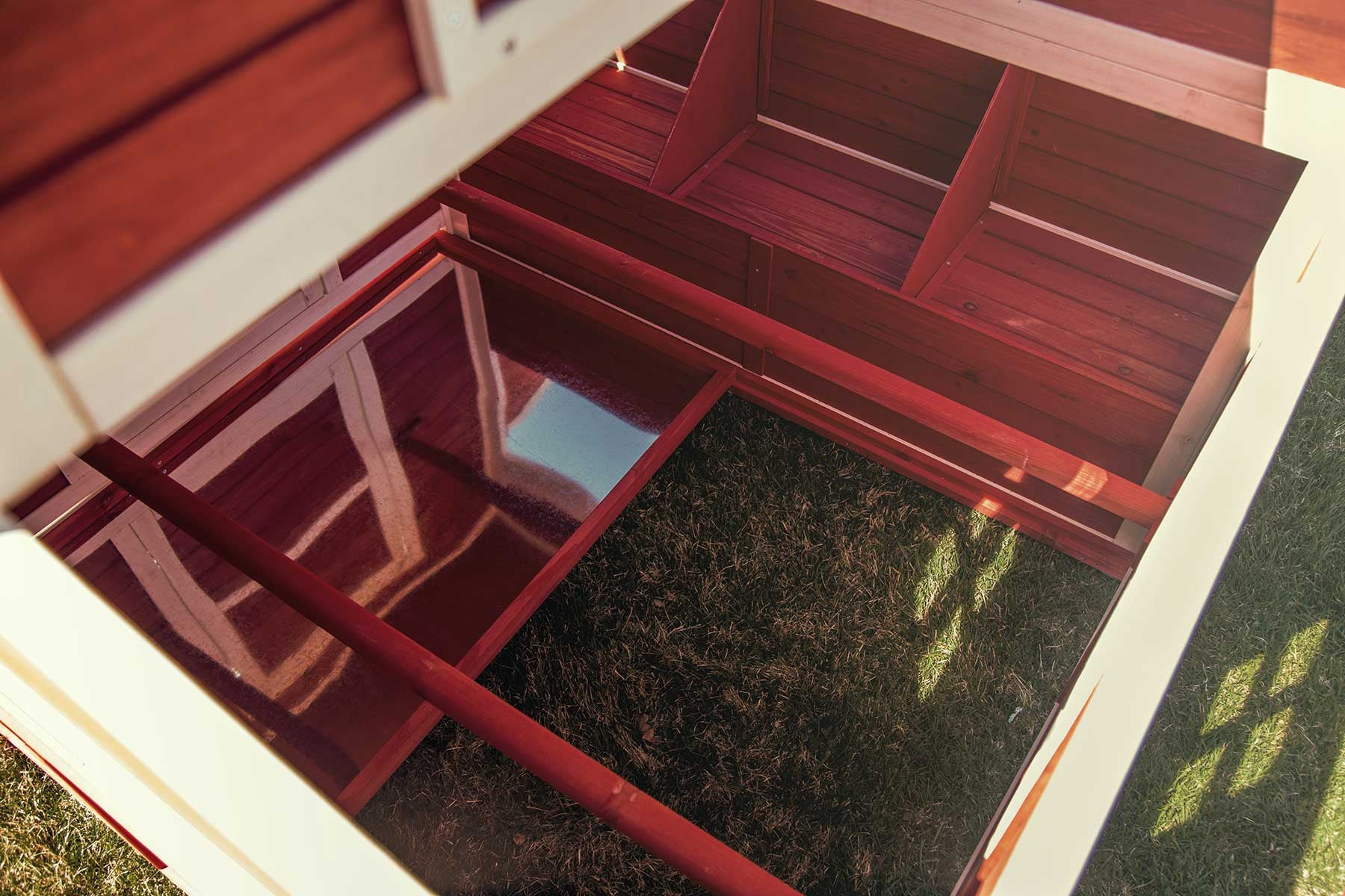 An interior view of the Schoolhouse chicken coop, showing roosting bars, sliding mess pans, and three nesting areas