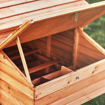A nesting box with the lid open, revealing the divider and nesting areas