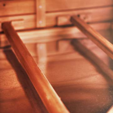 Closeup of thick rounded wooden dowels laid horizontally within a chicken coop interior