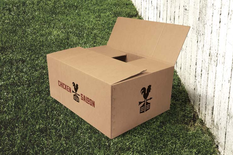 A corrugated cardboard box with Chicken Saloon logos on it, partially opened on a grassy lawn