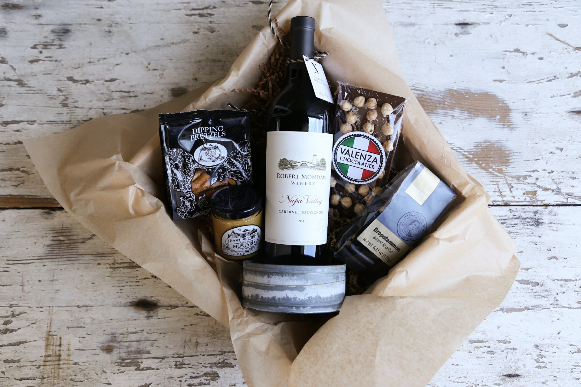 Gourmet Wine Gift: our personal favorite, this luxe crate contains wine, a wine coaster made from vintage materials, gourmet snacks & delicious Valenza chocolate. $125