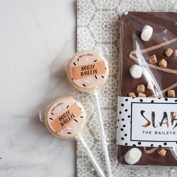 Baileys Chocolate & Lollipop Set - The Home Of Fully Loaded boozy Chocolate. Large Slabbs of boozy chocolate with a variety of alcoholic ganaches; gin, rum, whisky, amaretto, baileys and toppings. Available as monthly subscriptions.