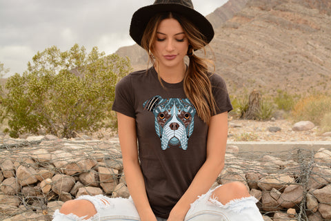 Model wearing a Bella tee in Brown featuring a drawing a boxer dog face filled with blue and brown symmetrical designs and patterns.