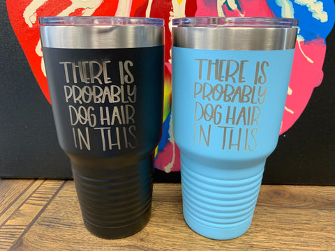 "Image of two travel mugs, one in black and one in light blue, both with metal rims at the top, clear plastic lids, and the words ""There is probably dog hair in this"" laser etched on the side."