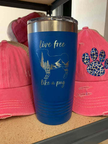 "Image of an insulated tumbler in Royal with metal rim, clear plastic lid, and a pug silhouette filled with a mountainous scenery and the words ""live free like a pug"" laser etched in the side of the cup."